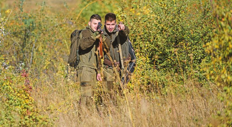 Army forces. Camouflage. Military uniform. Man hunters with rifle gun. Boot camp. Hunting skills and weapon equipment. How turn hunting into hobby. Friendship stock photography