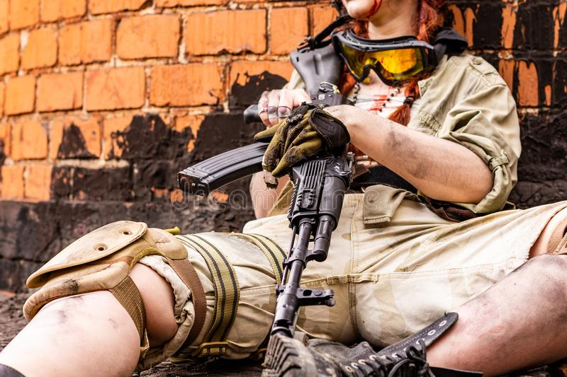 Army girl with rifle in camouflage clothes in urban scene, getting rest. Croped portrait, close up. Army girl with rifle in camouflage clothes in urban scene royalty free stock image
