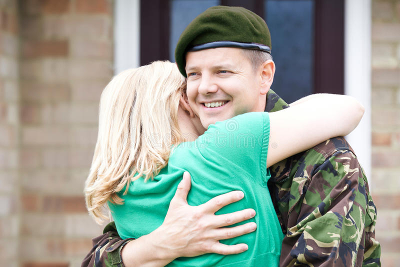 Army Husband Home On Leave Hugging Wife stock photo