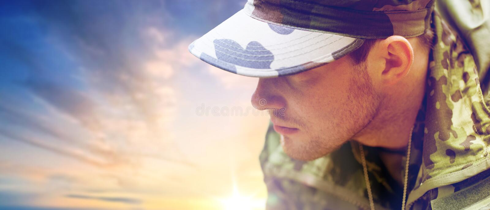 Close up of young soldier in military uniform. Army, national service and people concept - close up of young soldier in military uniform over sky background stock photos