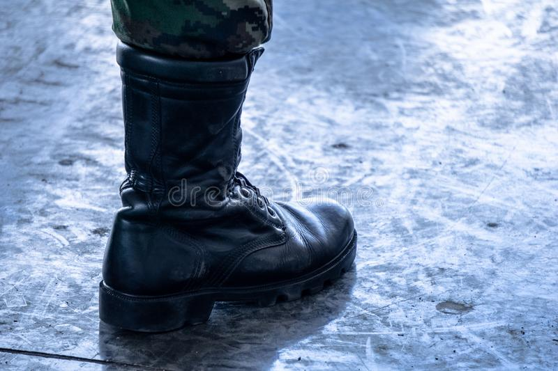 Army / Navy military boot with jungle camouflage pants in top boot stock photography