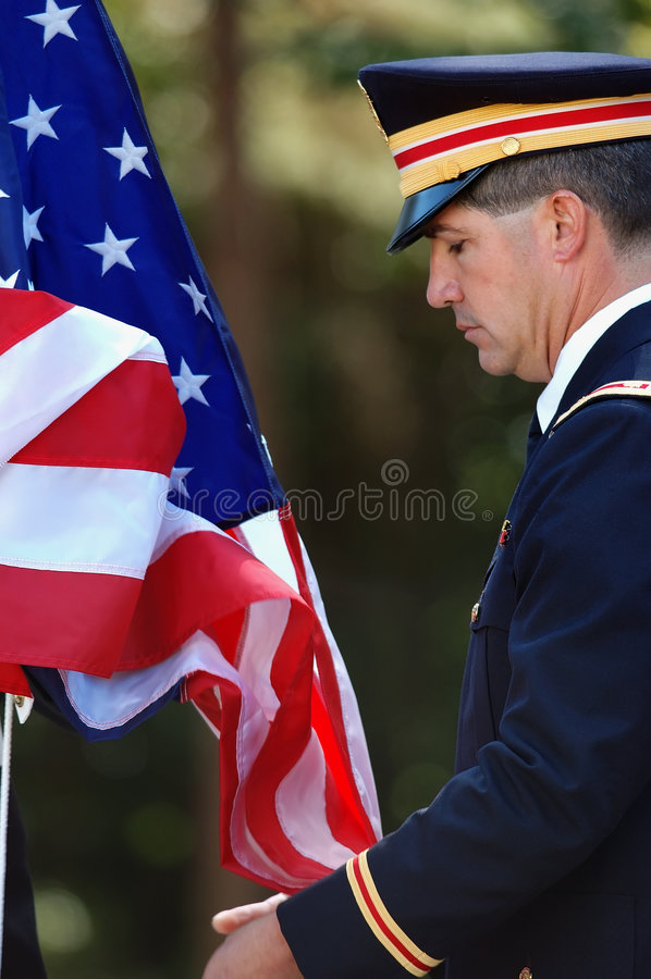 Army Officer Raising the Flag. Army officer assisting with the raising of the American flag royalty free stock images