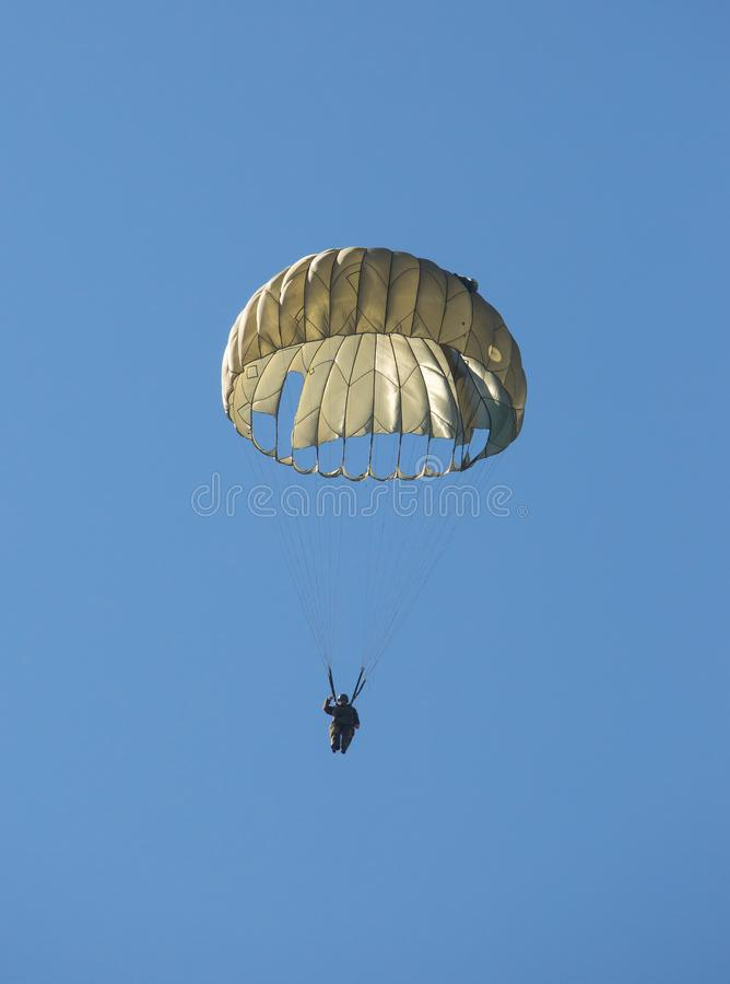 Army paratrooper floating to the ground below a parachute royalty free stock photos