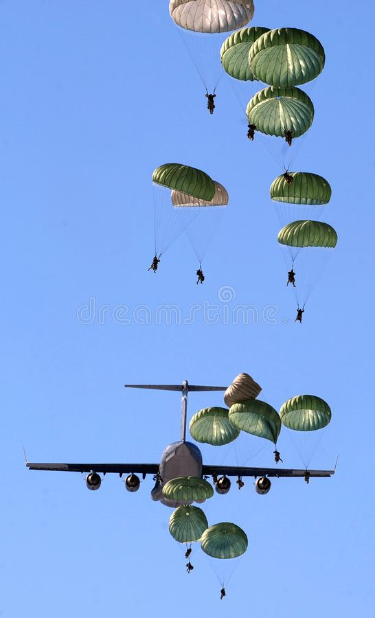 Army Paratroopers Practicing Parachute Drop from a Military Air Plane during Daytime royalty free stock photo