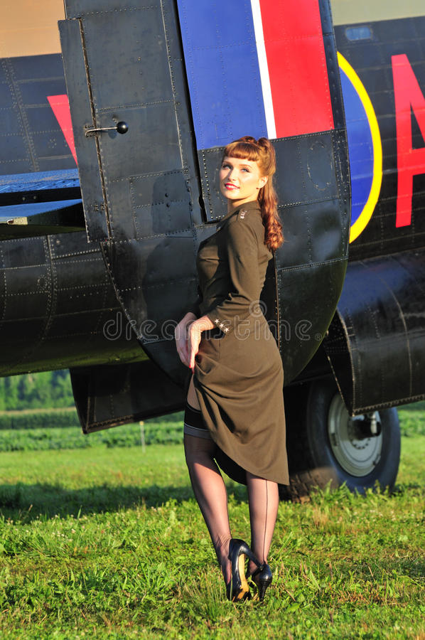 Army pinup girl with WWII bomber stock photography