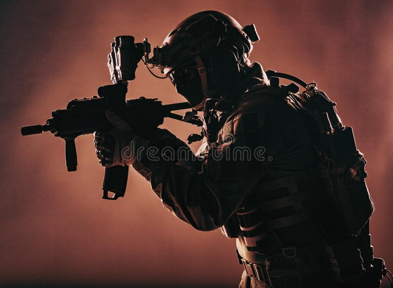 Elite forces soldier aiming with service rifle. Army soldier, counter terrorist squad fighter, military company mercenary in ammunition and body armor, helmet royalty free stock images