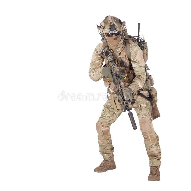 Army soldier crouching with rifle studio shoot. Modern army infantry rifleman in camo uniform, radio headset on helmet, ammo on load carrier, sneaking, crouching stock photography