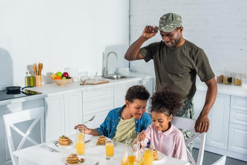 Army soldier father looking at happy kids enjoying meal royalty free stock photos