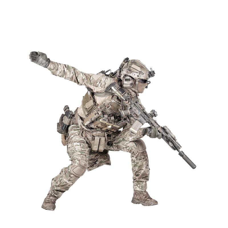 Army soldier going in attack isolated studio shoot. Army soldier, modern combatant, fireteam sergeant in battle uniform and helmet, armed with service rifle stock images