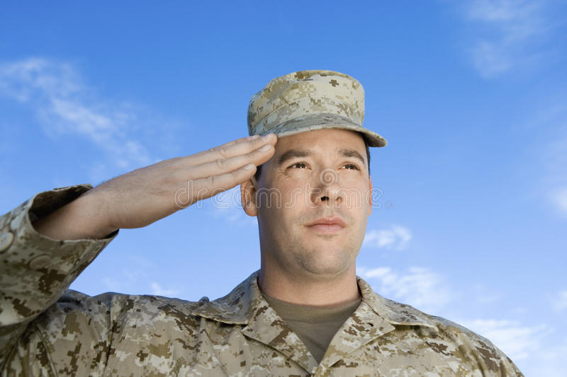 Army Soldier Saluting. Closeup of confident army soldier saluting against sky royalty free stock photography
