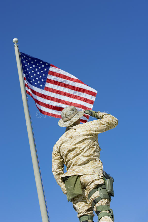 Army Soldier Saluting American Flag. Rear view of army soldier saluting American Flag against blue sky royalty free stock photography