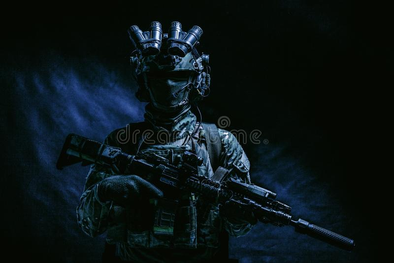 Army special forces fighter low key studio shoot. Half length, low key studio shoot of army soldier, marine infantryman in mask, camo uniform, equipped modern stock photo
