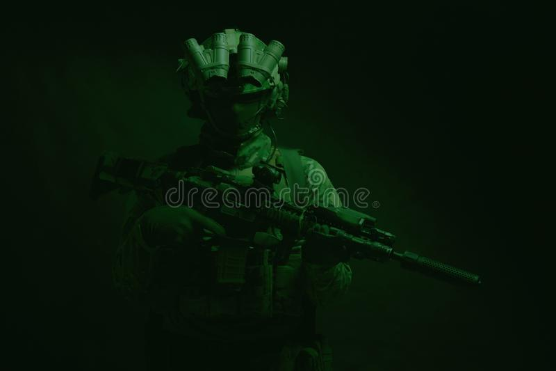 Army special forces fighter low key studio shoot. Half length, low key studio shoot of army soldier, marine infantryman in mask, camo uniform, equipped modern stock photography
