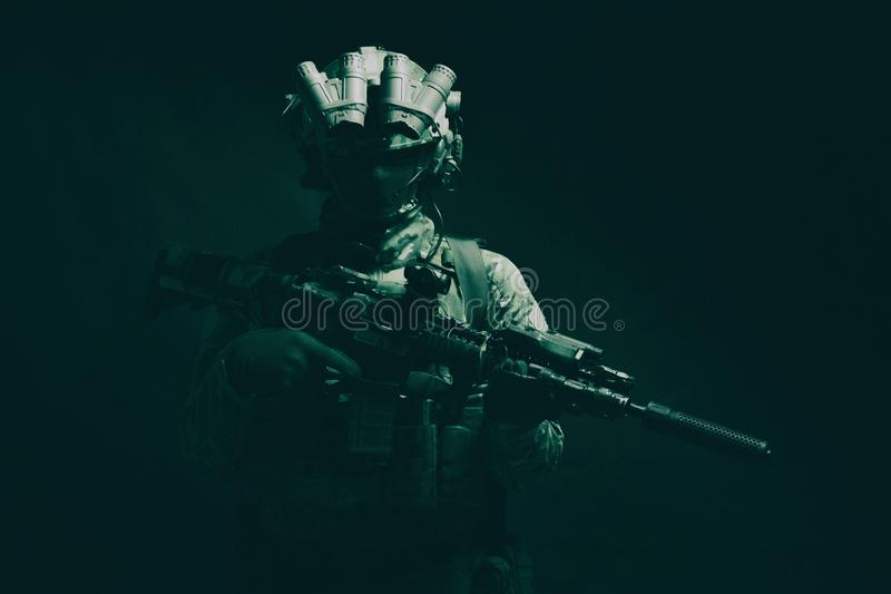 Army special forces fighter low key studio shoot. Half length, low key studio shoot of army soldier, marine infantryman in mask, camo uniform, equipped modern royalty free stock photo