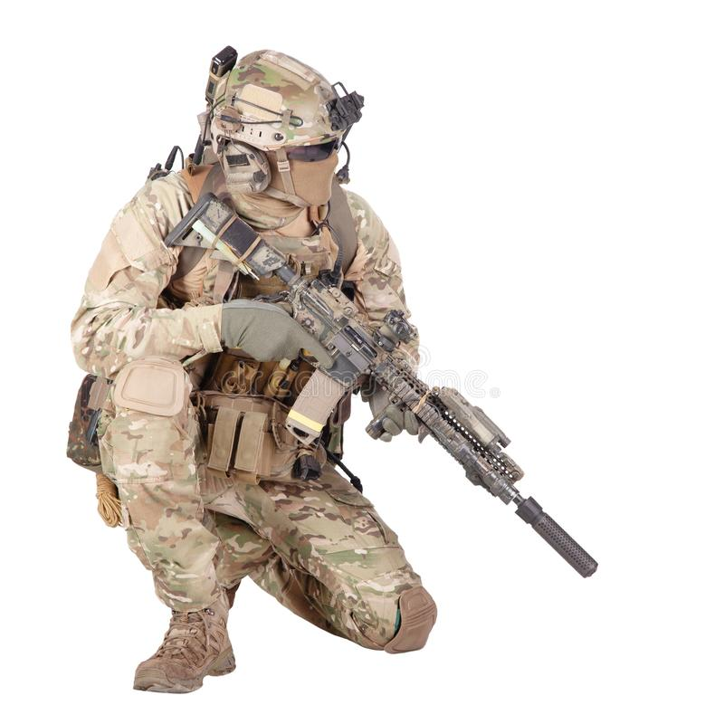 Soldier with rifle standing on knee studio shoot. Army special forces infantry in battle uniform, radio headset on helmet, armed service rifle, standing on knee royalty free stock photos