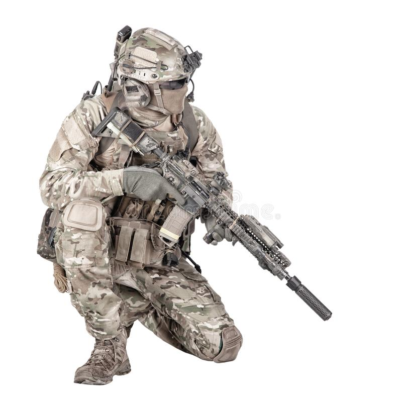 Soldier with rifle standing on knee studio shoot. Army special forces infantry in battle uniform, radio headset on helmet, armed service rifle, standing on knee stock image