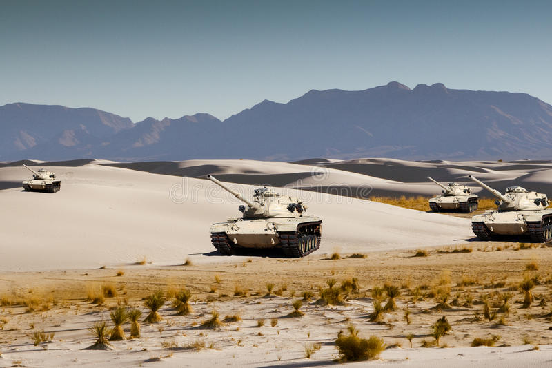 Army tanks maneuver in the white desert sand royalty free stock photography