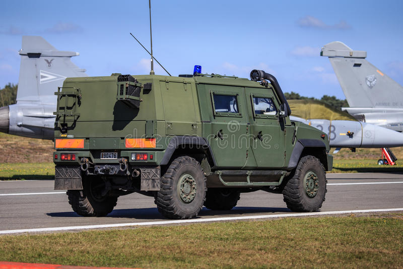 Army vehicle on patrol. Iveco LMV all-terrain vehicle of Belgian army patrolling a military airfield, with jet fighters in the background royalty free stock photography