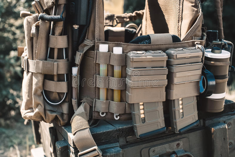 Army vest with a walkie-talkie, charged collars, stun grenades, luminous sticks. Standing on a wooden box of ammunition stock photo