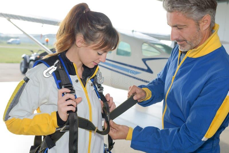 Arnés de la cerradura del instructor en paracaidista femenino foto de archivo