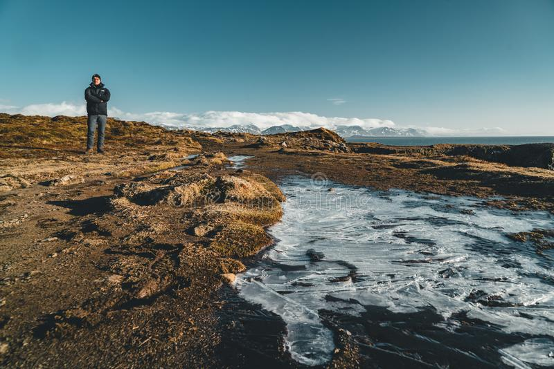 Arnarstapi, Islande - mai 2018 : Jeune touriste masculin se tenant près d'un petit champ de glace un beau jour avec le ciel de bu images stock
