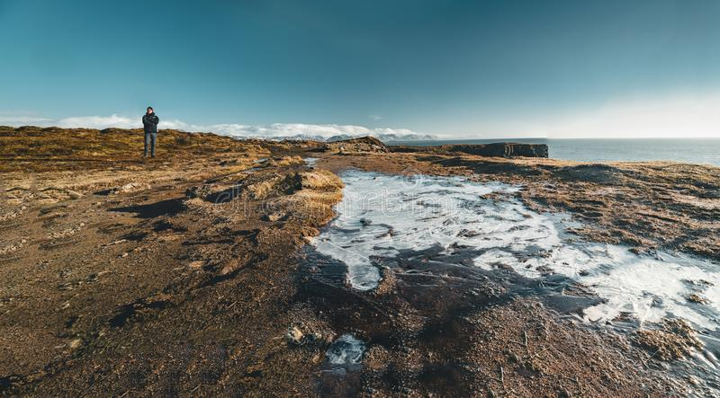 Arnarstapi, Islande - mai 2018 : Jeune touriste masculin se tenant près d'un petit champ de glace un beau jour avec le ciel de bu photographie stock libre de droits