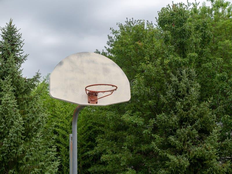 Aro de baloncesto de acero de la reducción que falta su red en día cubierto imagen de archivo libre de regalías