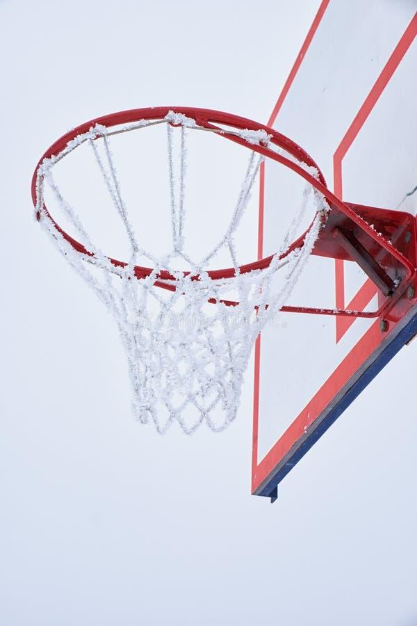 Aro de baloncesto con la red, cubierta por la escarcha fotos de archivo libres de regalías