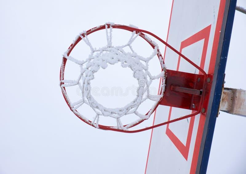 Aro de baloncesto con la red, cubierta por la escarcha foto de archivo