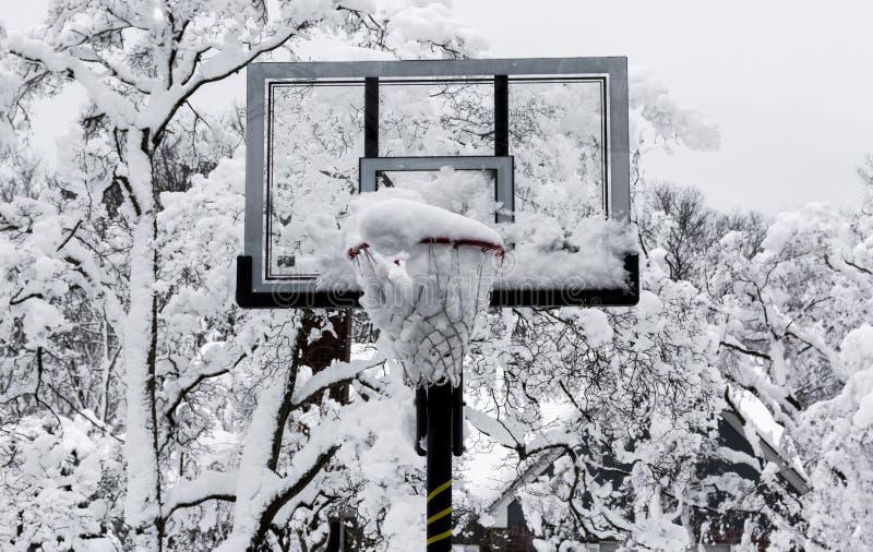 Aro de baloncesto con nieve en ella después de una tormenta fotografía de archivo
