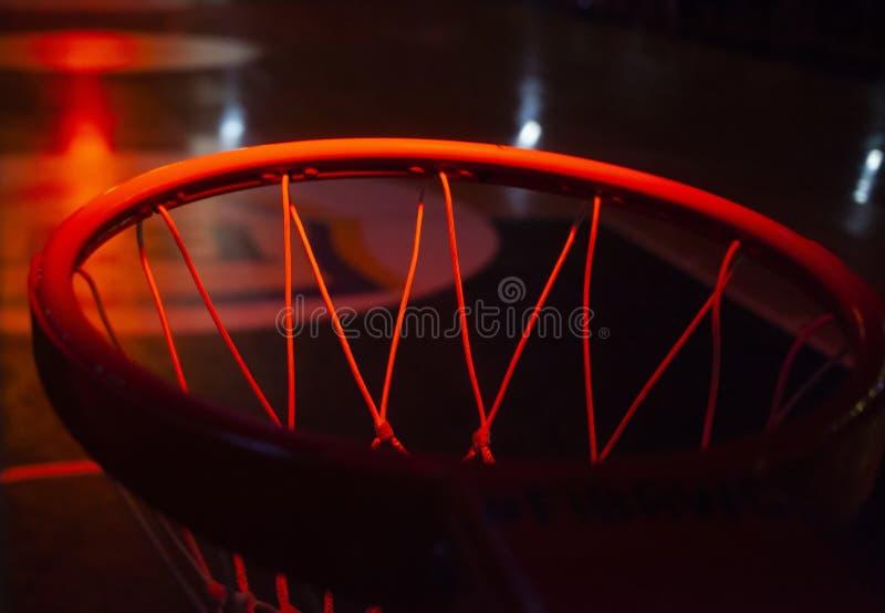 aro de baloncesto en luces de neón rojas en arena deportiva durante juego imagenes de archivo