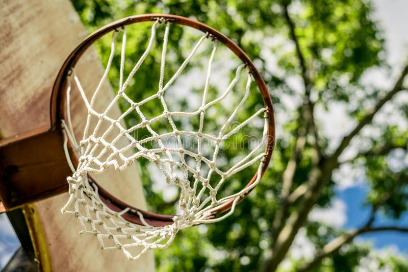 Aro de baloncesto viejo contra un fondo de árboles imagen de archivo