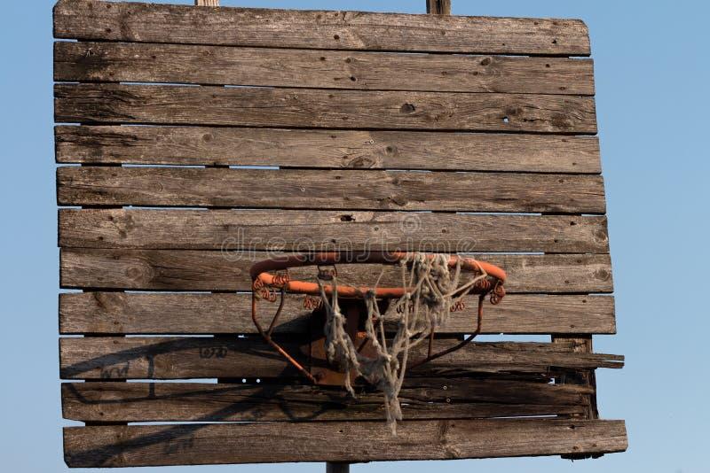 Aro de baloncesto viejo y oxidado con la red enredada foto de archivo