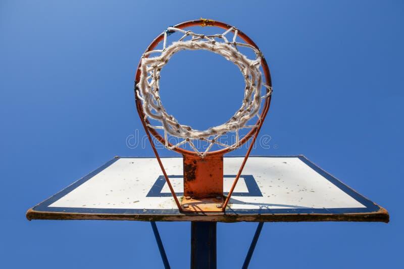 Aro de basquetebol velha contra o céu azul de baixo de foto de stock