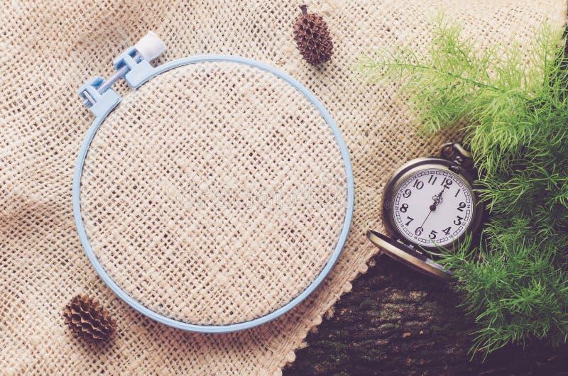 Aro de bordado com o saco vazio de serapilheira, e relógio de bolso do vintage foto de stock royalty free