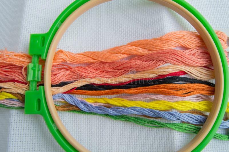 Aro de bordado con la lona e hilos de coser brillantes para el bordado de la tabla en el fondo blanco, visión superior foto de archivo libre de regalías