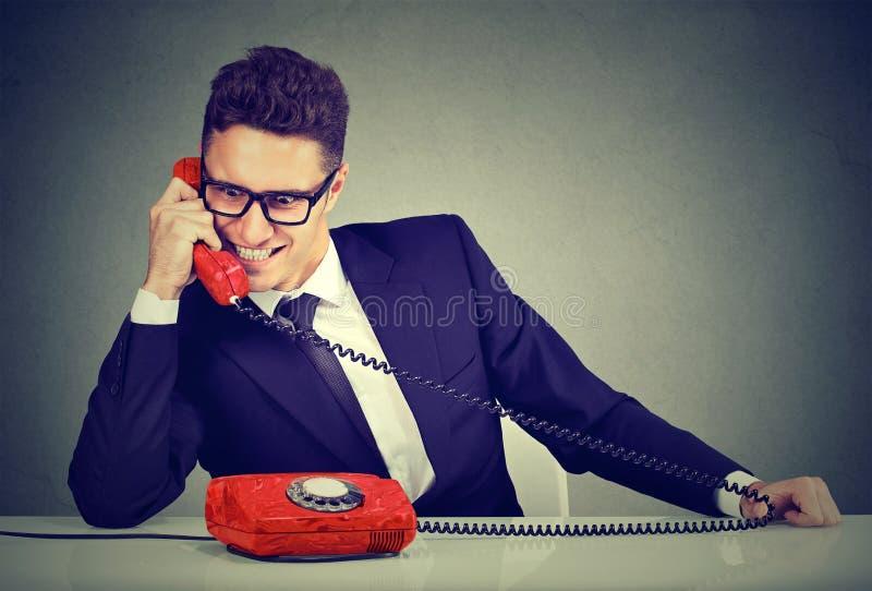 Aroganckiego sprzedawcy biznesowy mężczyzna reklamuje jego najlepszy produkt na telefonie obraz royalty free