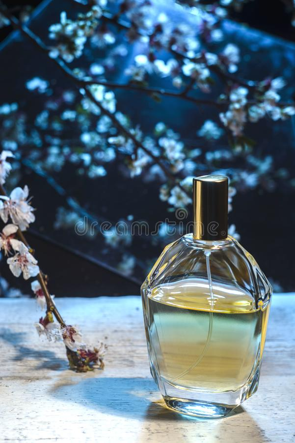 Men's perfume on a wooden table on a floral background royalty free stock photos