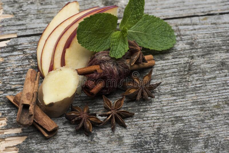 Aroma and cosiness concept. Spices placed on scarf, closeup. Anise, mint leaves, apple slices, ginger, cinnamon sticks and carnation on soft brown cloth royalty free stock image