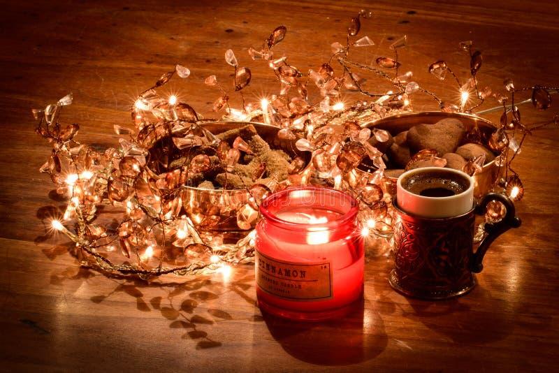 Aroma del coffea e della cannella con i biscotti di Natale ed il pane dello zenzero sulla tavola di legno, illuminata dalle luci  fotografie stock