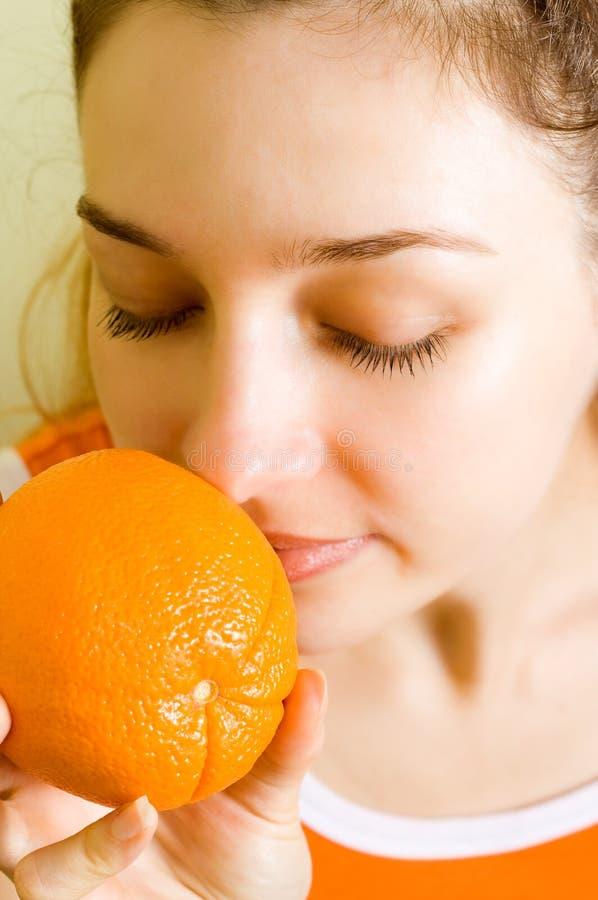 Aroma fruit therapy - woman smelling orange stock image
