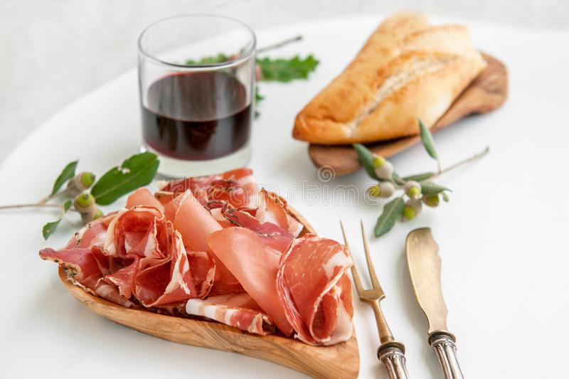 The aroma of ham and spices, thinly sliced on a white table with bread and antique Cutlery royalty free stock photography