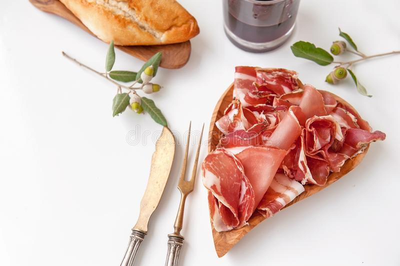 The aroma of ham and spices, thinly sliced on a white table with bread and antique Cutlery royalty free stock image