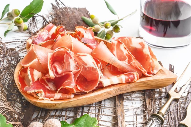 The aroma of ham and spices, thinly sliced on a white table with bread and antique Cutlery stock image