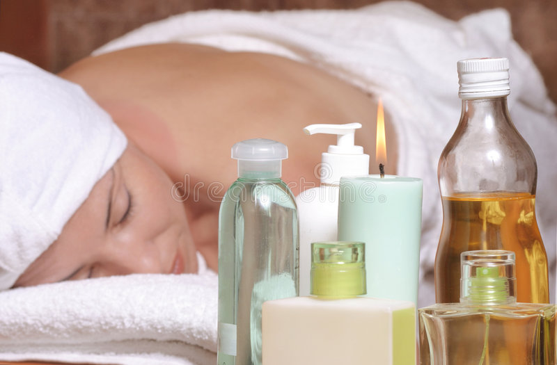 Aroma massage. Woman on massage table with oils, essential oils, candles, scents. Focus on products