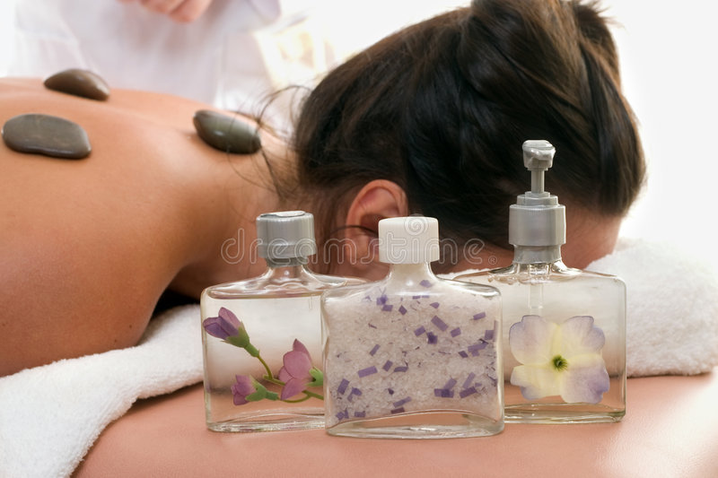 Aroma Products day spa. Assorted decorative scented products in focus by a woman relaxing at a day spa stock photos