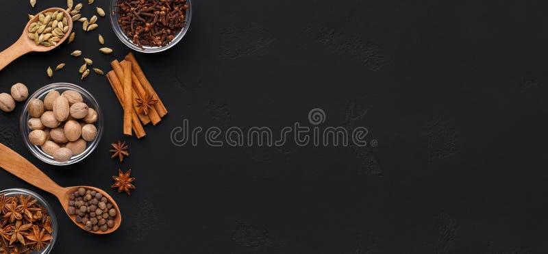 Aromagewürze für Weihnachtsgebäck auf schwarzem Hintergrund stockfoto