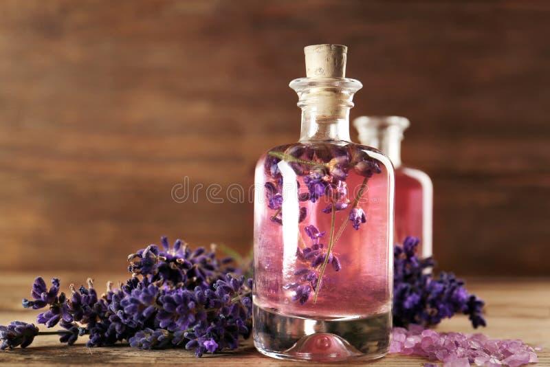 Aromaolie, overzees zout en lavendelbloemen op houten achtergrond stock afbeeldingen