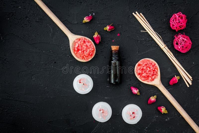 A aromaterapia para relaxa o conceito Botões de Rosa, sal dos termas, velas e óleo no copyspace preto da opinião superior do fund fotos de stock