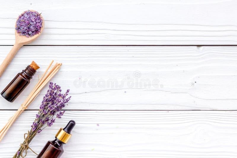A aromaterapia para relaxa o conceito Ramo da alfazema, sal dos termas e óleo no copyspace de madeira branco da opinião superior  fotos de stock